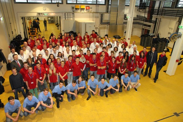 The participating students (wearing red-T-shirts) and their teachers (in white) building the Austrian flag in the grape reception hall of the HBLA's winery